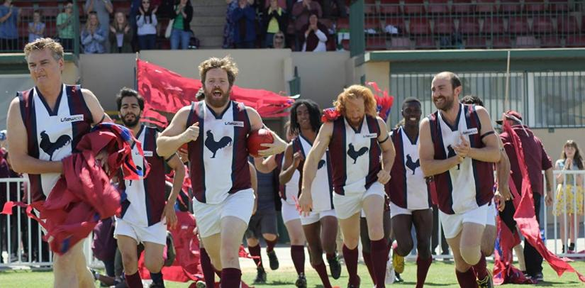 A mens football team running onto a field