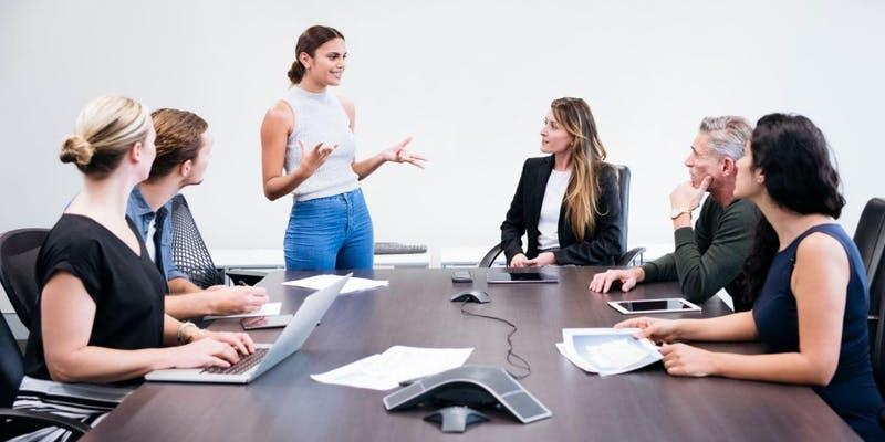 Woman standing and talking to people seated at boardroom table
