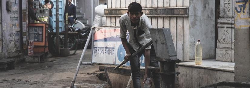 Young man pumps water from a well in a village street