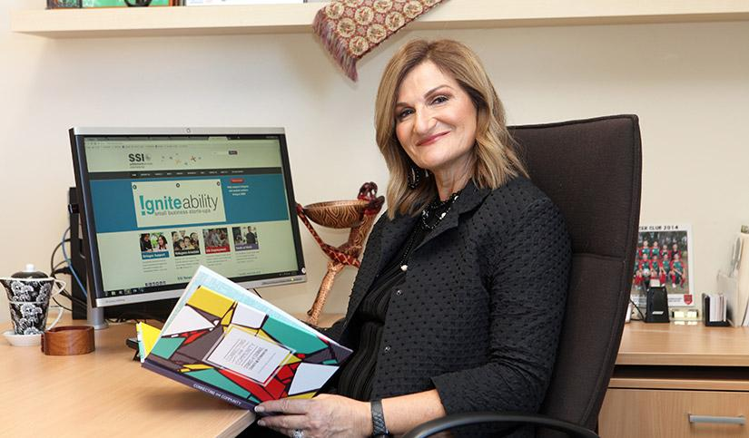 Violet Roumeliotis sitting whilst holding a book with a computer screen on in the background