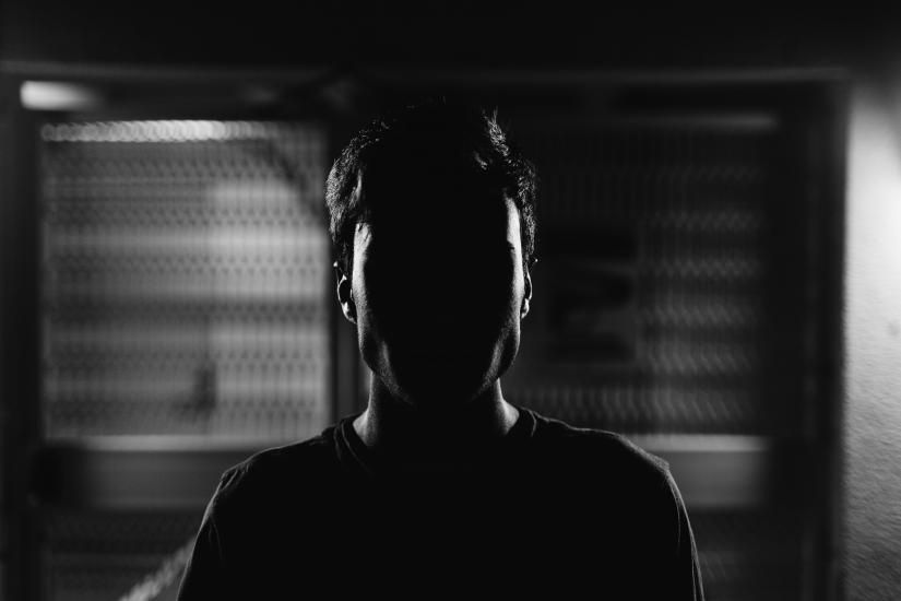 witness with face in darkness
