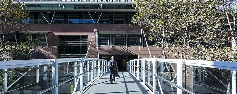 A man walks along a pedestrian foot bridge towards a large building with peach coloured walls