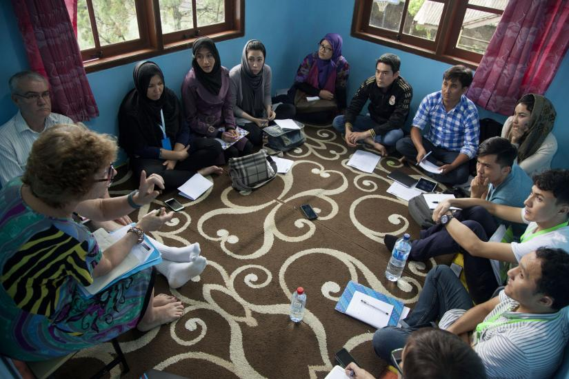 A group of refugee teachers sitting on the floor of a classroom