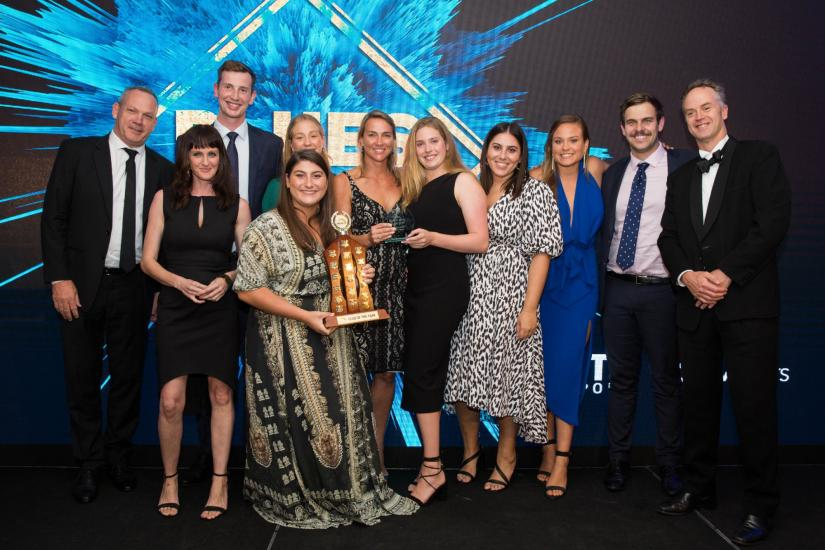11 people from the UTS Club of the Year in formal wear, smiling and holding a trophy