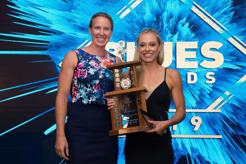 Former Sportswoman of the Year, Jo Brigden-Jones, presents Gabriella O'Grady with the Sportwoman of the Year award. They are both wearing formal wear and smiling at the camera