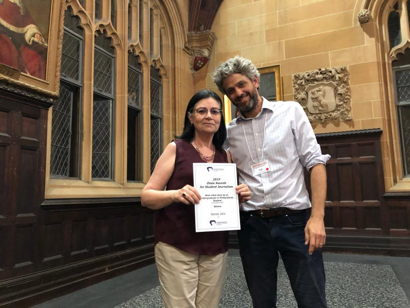 Monica Attard accepts a certificate from a man