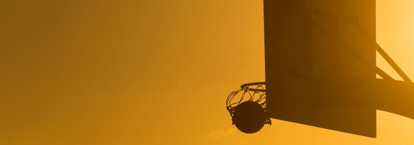 A basketball hoop with an orange sky in the background.
