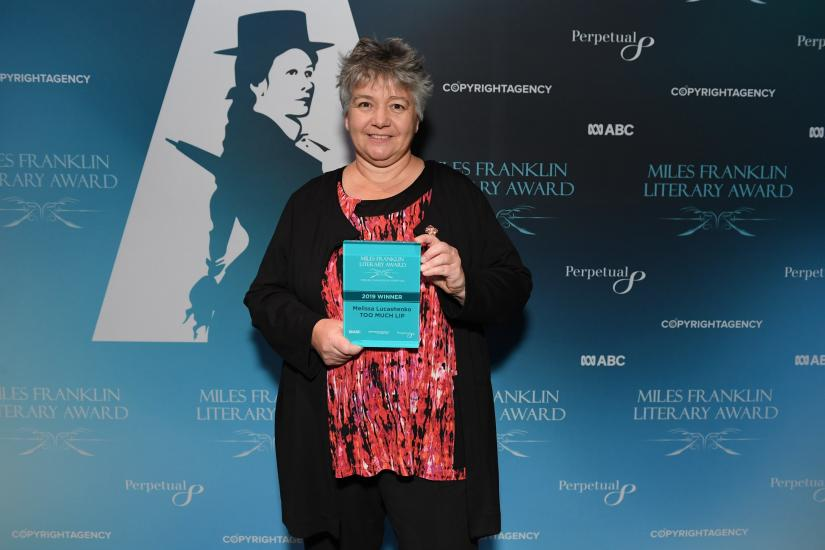 Melissa Lucashenko posing with the 2019 Miles Franklin Literary Award