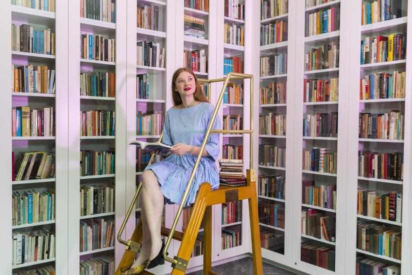 Bri sitting on a ladder surrounded by bookshelves