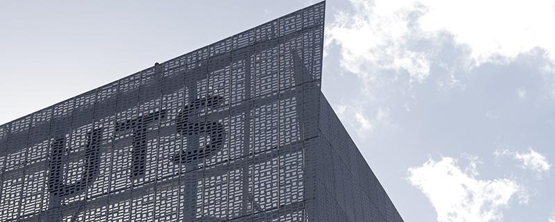 A UTS logo on top of a building covered in aluminium screens perforated with binary code ones and zeros