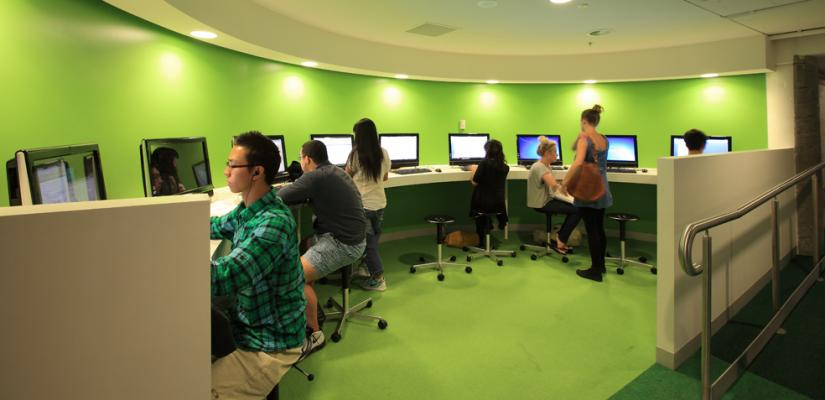 Students sit at computer along a curved bench, n a room with green walls and green carpet