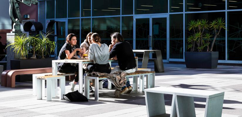 Students sit at a picnic table in an outdoor terrace, surrounded by sculpture and pot plants