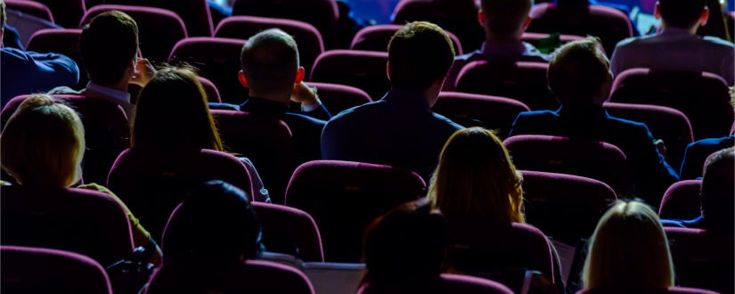 Rows of people sitting in a dark theatre