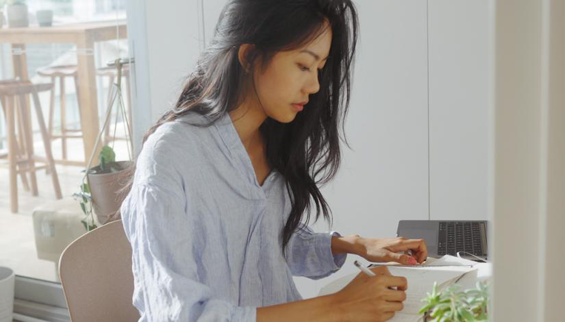 Rachel Tse working at a desk in a light cafe setting