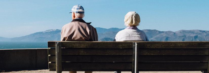 An elderly man and woman sit on a bench looking out to sea.