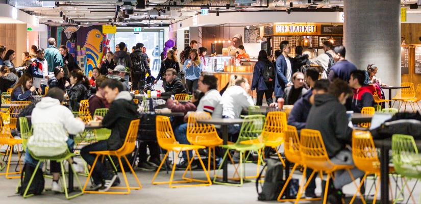 A crowded food court with colourful chairs and neon-lit takeaway counters