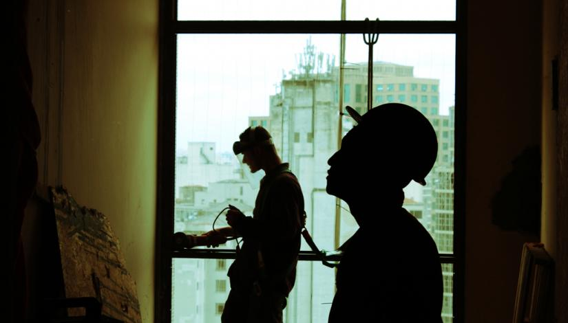 Silhouette of two construction workers inside a building