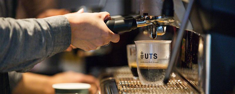 Hands reach out to an espresso machine where a UTS keep cup is filled with coffee