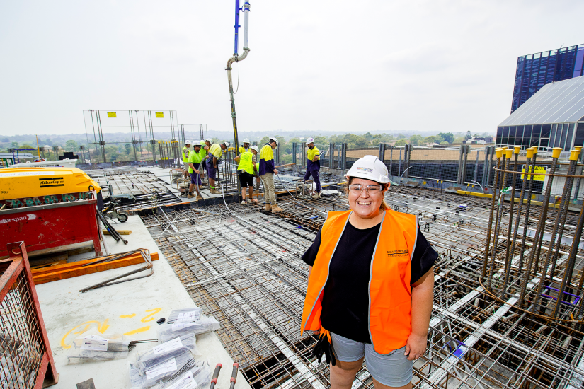 Young woman in hard hat and orange vest stands leading a team of men on a construction site