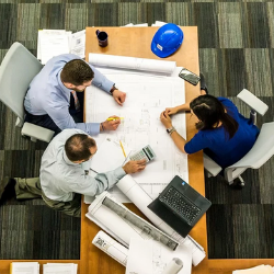 Three colleagues sit around a table working on a large piece of paper
