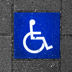 Wheelchair user sign on pavement