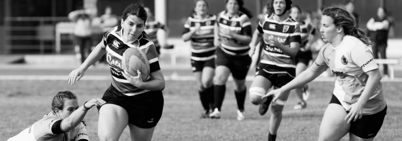 A woman escapes a tackle and runs down the field carrying a rugby ball.