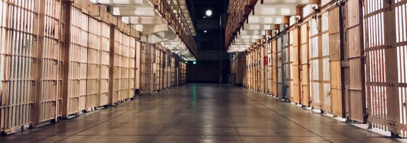 A picture of empty rows of prison cells.
