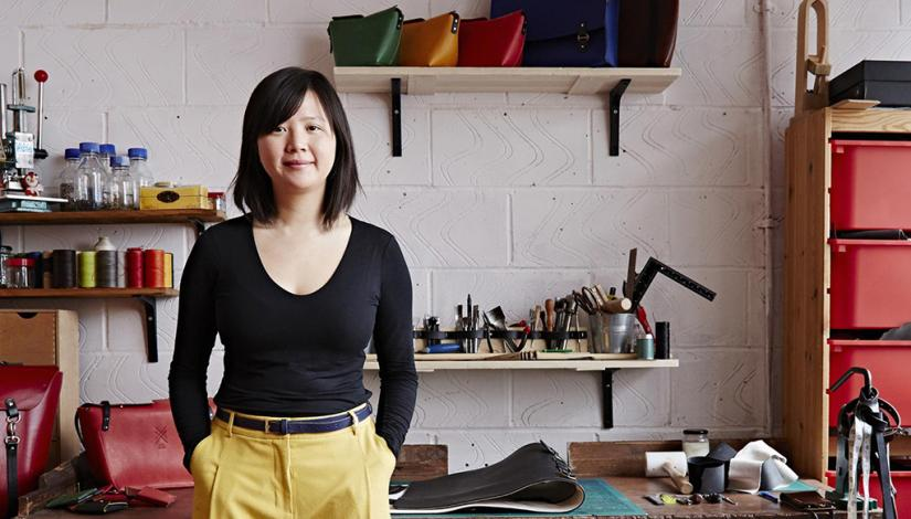 Candice Lau in her workshop surrounded by tools and finished bags.