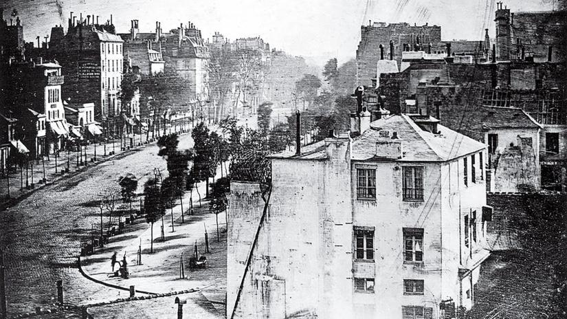 Grainy black-and-white photo of a Paris street with two figures visible