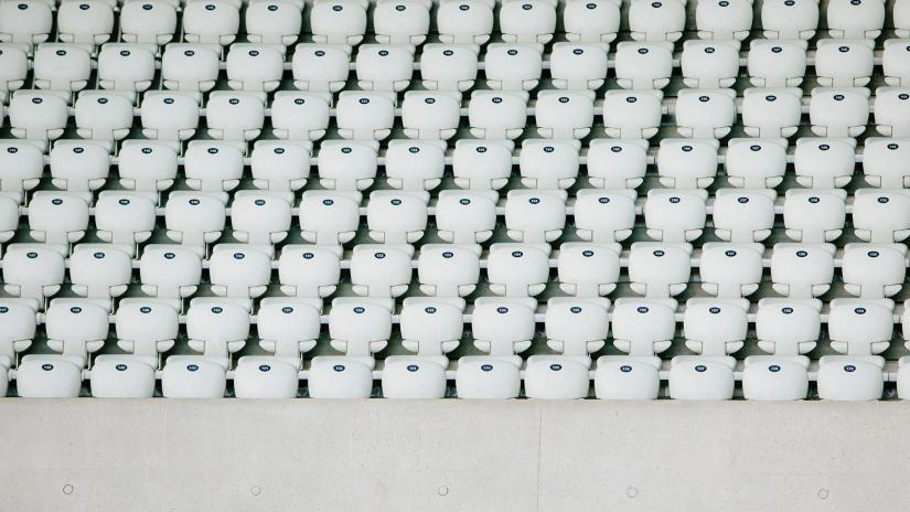 Hundreds of empty white seats in a sporting stadium