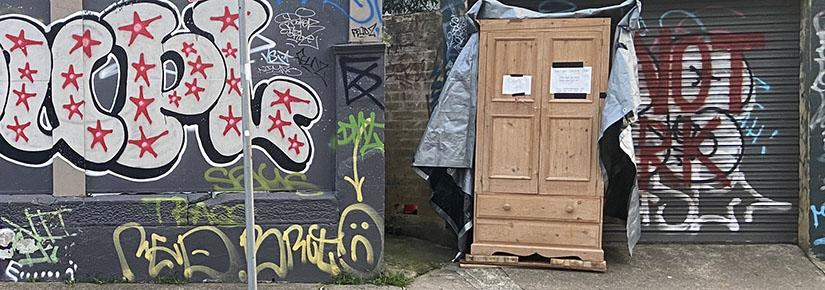 "On a street with graffiti, a light brown cupboard sits with a sign that says ""leave what you can, take what you need"""