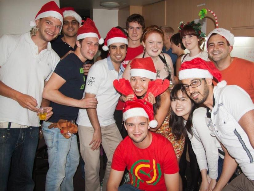Seref with friends from UTS Housing wearing red Christmas Santa hats