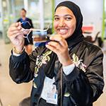 Young high school girl wearing a head scarf smiling while showcasing a project she worked on.