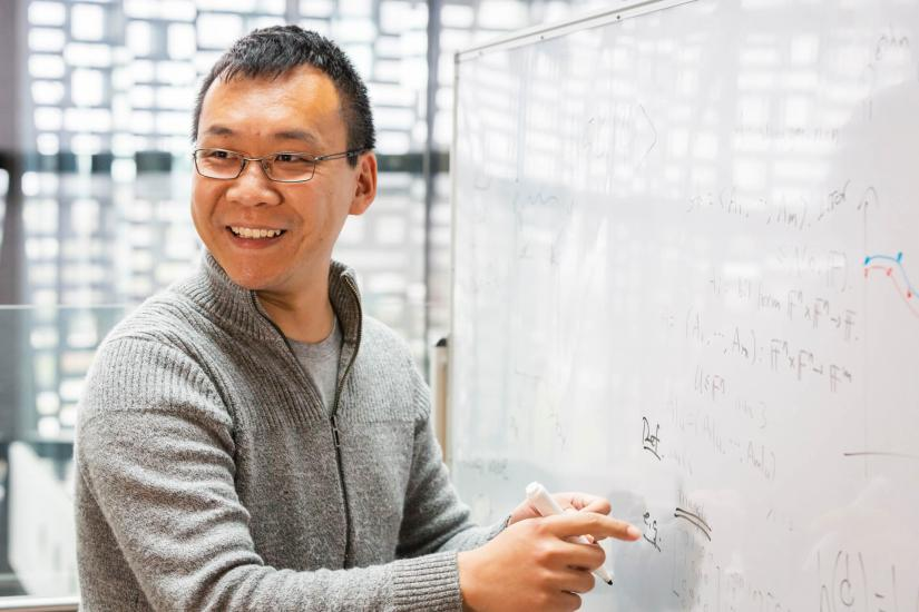 QSI Dr Youming Qiao writing quantum algorithms on a whiteboard and smiling while looking to his right