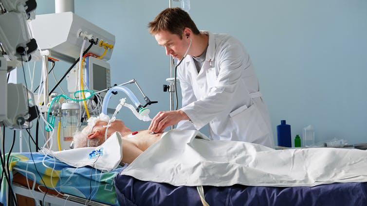 Doctor checking a patient who is using a ventilator