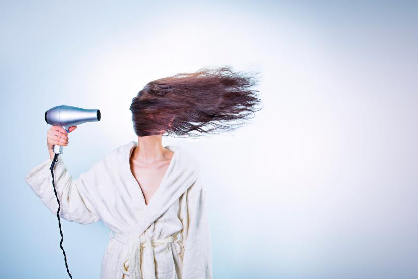 Woman in bathrobe blowdries her hair across her face