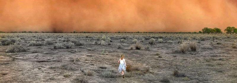 A young girl runs across a drought-stricken landscape towards a wall of dust.