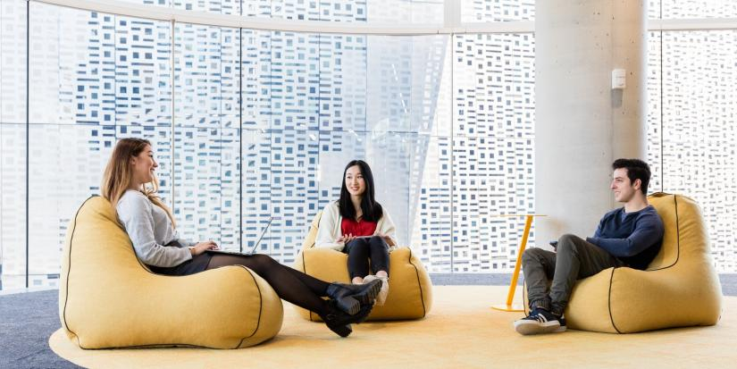Students sit apart on yellow beanbags, with a large glass window behind them