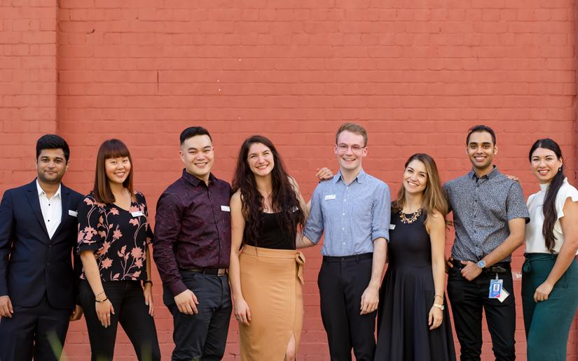 Group of young alumni standing in front of brick wall