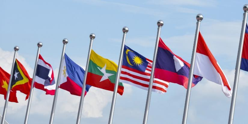 Nine flags of different Indo-Pacific countries, flying against a blue sky