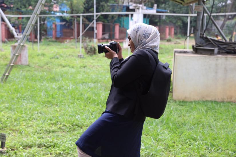 Image of Amaani in profile. Full body image. Amaani is holding a camera and is looking at the back of it as if she is either checking the lens, or checking the last digital image that she took. She is standing in an area with green grass, surrounded by fencing.