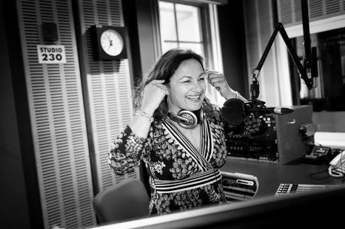 Black and white image of Jill Emberson at the radio presenting desk for the ABC. Jill is laughing in this image. She is sitting close to the microphone and wearing headphones.