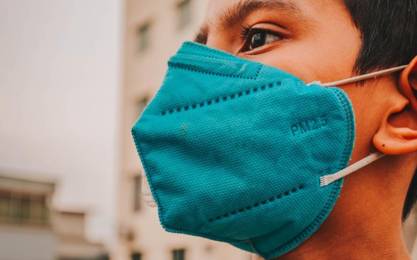 boy wears a N95 face mask in the street.