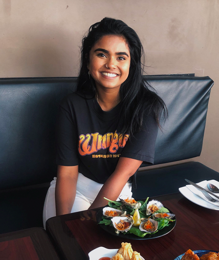 Smiling girl sitting at table with plates of food