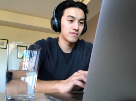 Young man wearing headphones using a laptop next to a large glass of water
