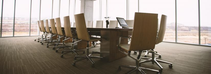 an empty boardroom desk and chairs