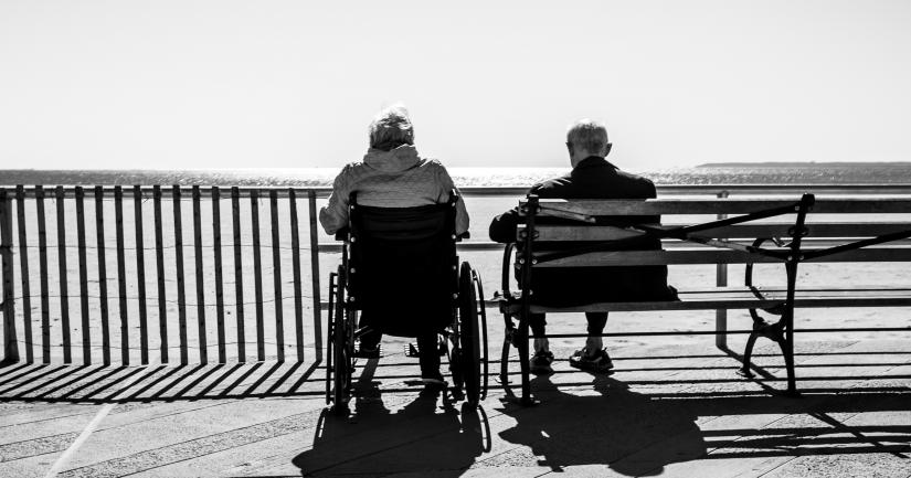 a woman in a wheelchair and a man on a bench look out over the ocean.