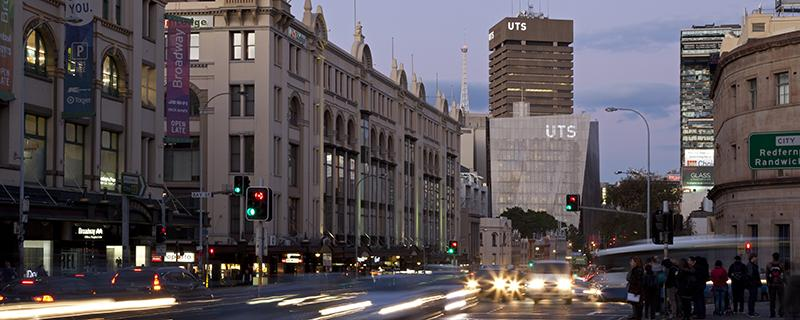 A view down Broadway at dusk, with the UTS Faculty of Engineering and IT building and UTS Tower lit up