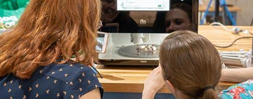 Two women watch the Foodini 3D printer print food
