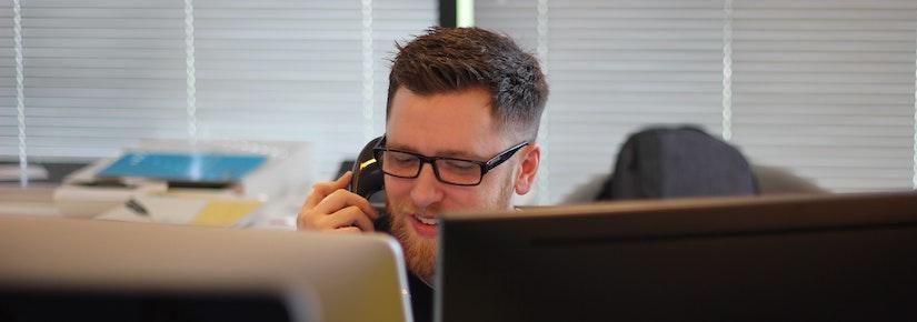 Man on phone looking at dual computer screens